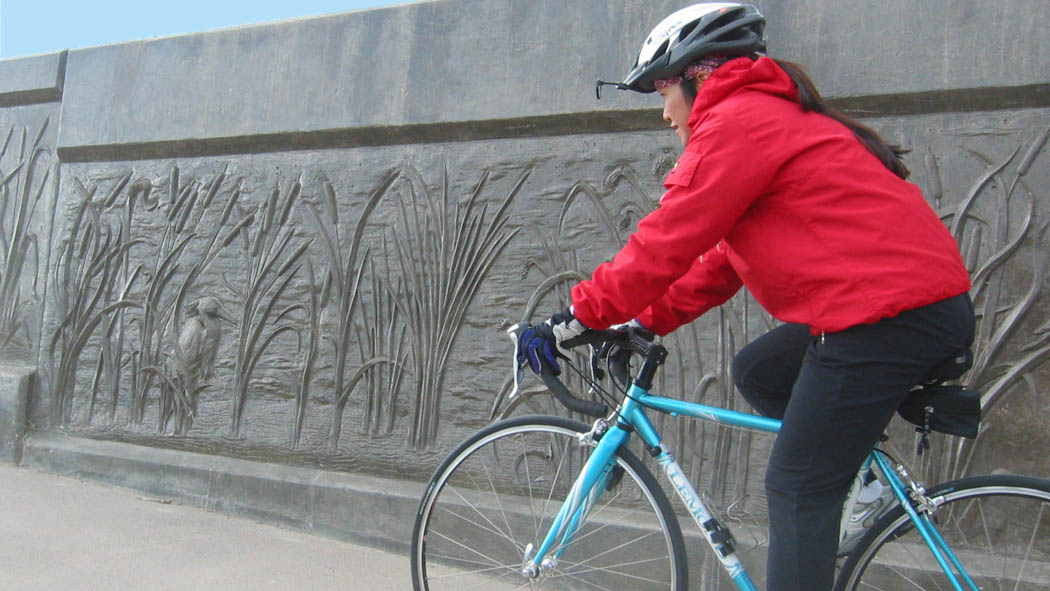 Woman riding a bicycle next to a wall