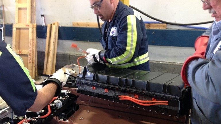 mechanics working on hybrid battery